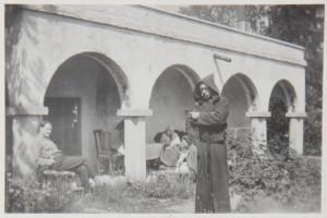 Akseli Gallen-Kallela munkinkaavussa Tarvaspään pihalla ja ateljeelinnan loggian (pylväskäytävän) alla Jorma ja Mary Gallen-Kallela sekä Maryn äiti Aino Slöör. Kuvan on ottanut Kirsti Gallen-Kallela toukokuussa 1928.